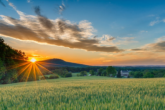 A perfect Spring day ends as the sun sets and sprays warm golden light over a beautiful farm with fields sprouting, a stone house, and mountain ridges in the background.
