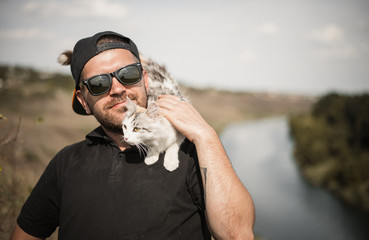 a bearded man in a black baseball cap, black shirt and shorts playing with white fluffy cat on top of a cliff on the background of the river and the forest