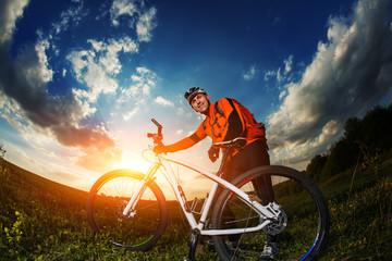 wide angle portrait against blue sky of mountain biker Cyclist