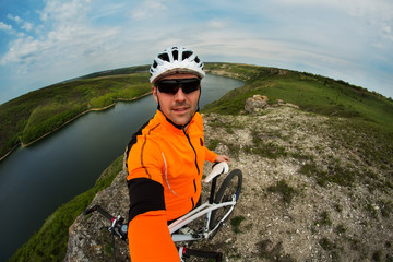 Cyclist in Orange Wear Riding the Bike above River