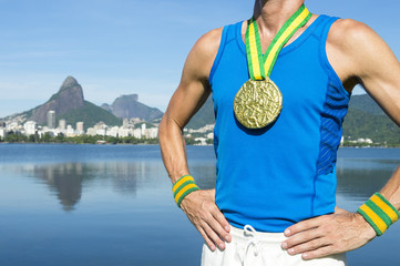 Gold medal athlete stands in front of a calm morning view of Lagoa Rodrigo de Freitas lagoon in Rio de Janeiro, Brazil