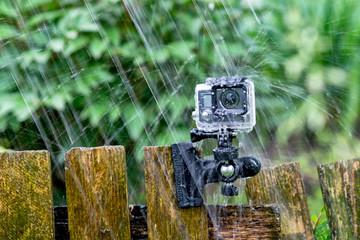 Action camera under heavy rain on nature background