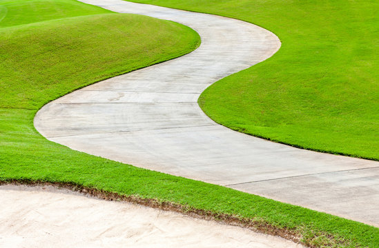 Path curving through green grass in golf course.