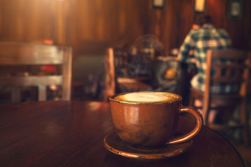 Cup of coffee on table in cafe with people vintage instagram effect - shallow depth of field