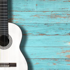 White classical guitar on vintage wood background with copy space.