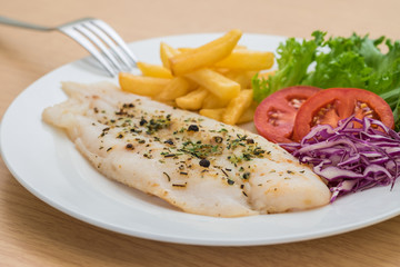 Grilled fish fillet steak with herb and french fries on plate