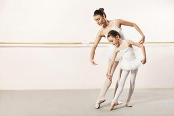 Little ballerina dancing with ballet teacher in dance studio