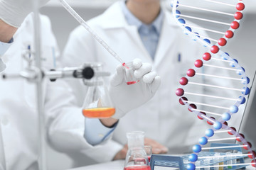 close up of scientists filling test tube in lab