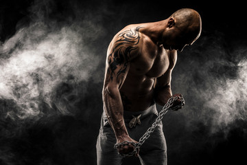 Strong bald man trying to tear metal chain