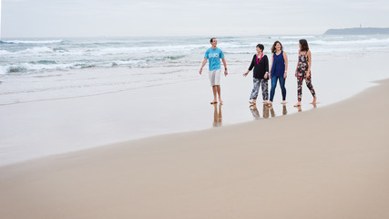 Family of four walking towards camera on the beach