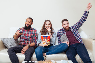 Friends eating popcorn and watching tv together