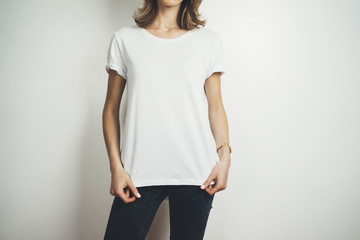 Cropped image of young hipster girl wearing blank white t-shirt and black jeans, mock-up of balnk white t-shirt, white background