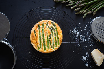 Asparagus tart with egg and cheese filling on the cooling rack. Selective focus.