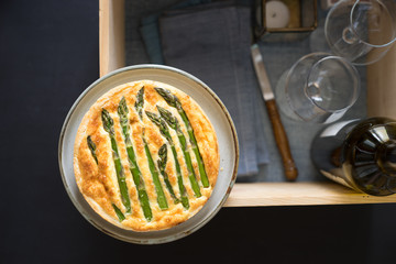 Asparagus tart with egg and cheese filling on wooden box with glasses and wine bottle prepared for picnic. Selective focus on the tart surface.