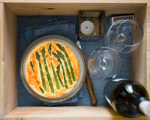 Wooden box prepared for picnic: asparagus tart, two wine glasses, wine bottle, candle. Selective focus on tart.