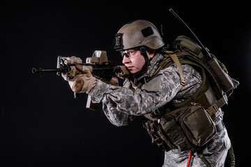 US Marine with gun/US Marine in uniform,helmet, body armor with rifle on black background