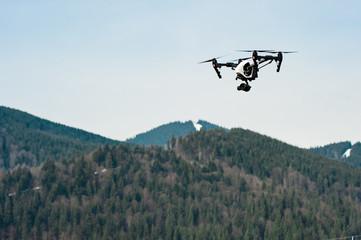 flying drone with camera/Drone with camera hovering over mountains