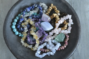 Healing properties of gemstones and crystals on a pottery bowl with wooden background