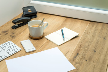 Wooden workspace with office supplies and coffee
