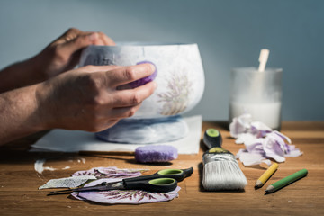 Decoupage hobbyist hands decorating a vase with lavender pattern - some artistic supplies on a table.  Wall mural