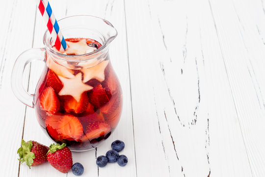 Red, White and Blue Lemonade or Sangria. Patriotic drink cocktail with strawberry, blueberry and apple for 4th of July party