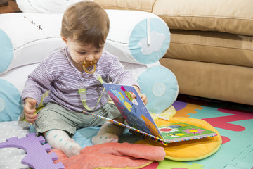 Little child looking at colorful book at home