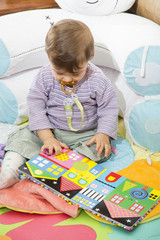 Baby looking down at colorful book with pictures