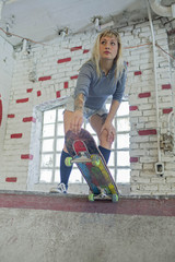 Young woman with skateboard standing at basement skate park