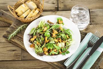 Mediterraner Salat mit Pfiferlingen auf weißem Teller
