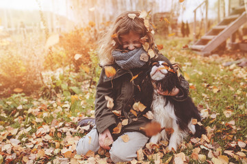 happy child playing with her spaniel dog in autumn