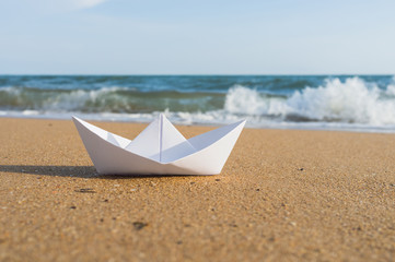 white paper boat on beach