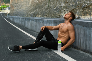 Sports. Tired Exhausted Athletic Man With Fit Muscular Body In Sportswear Resting After Running Outdoors. Topless Handsome Healthy Male Runner Taking Break After Fitness Workout And Exercising.