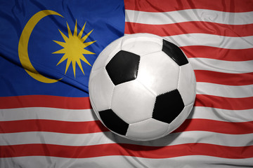 black and white football ball on the national flag of malaysia