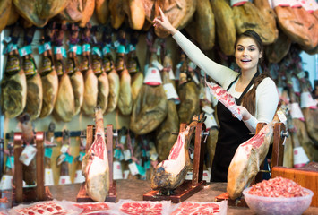 butcher with lard and meat in counter of store