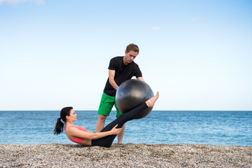 Sport und Fitness Instruktor zeigt junger Frau wie man mit Gymnastikball den Bauch trainiert am Strand im Freien