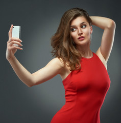 Woman in red dress making selfie photo by phone