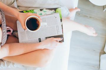 Junge Frau liegt im Bett und liest Zeitschrift