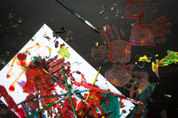 Mess of paints and brushes on table