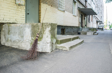 Wooden broom of dry twigs stands at the porch of houses on the pavement