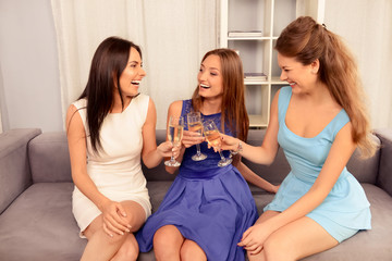 Pretty girls sitting on sofa and clinking with glasses of wine