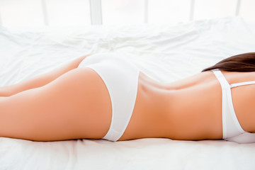 Close up photo of slim girl with  beautiful skin lying on bed