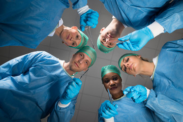 Surgeons With Medical Instruments Looking At Camera