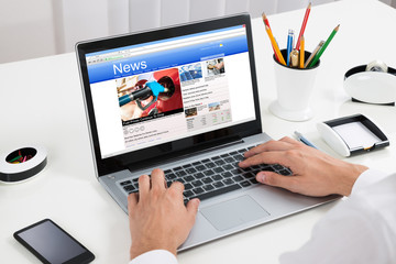 Person Reading News On Laptop