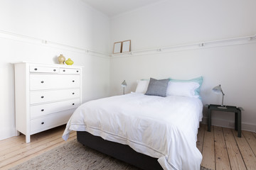 White bedroom with decorator items in beach styled home apartmen