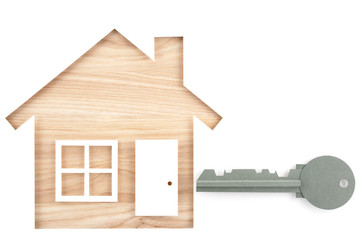 House and key shaped paper cutout on natural wood lumber. Isolated on white background.