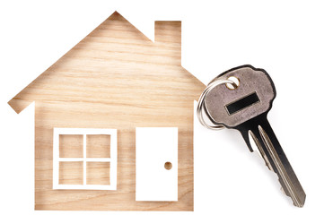 House shaped paper cutout and key on natural wood lumber. Isolated on white background.