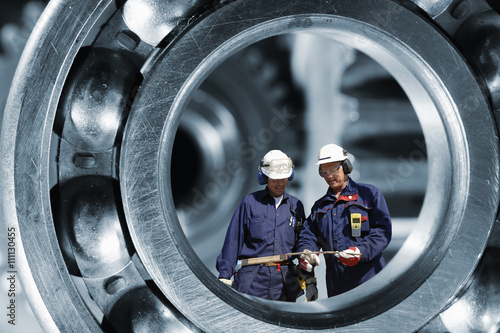 Wall mural industrial engineering parts with two workers inside giant ball-bearing