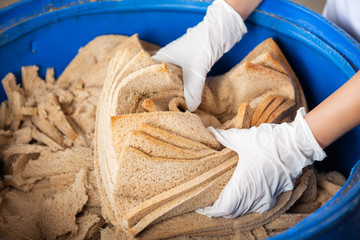 Baker's Hands Discarding Bread Waste In Garbage Bin