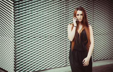 Red-haired girl model stands near wall in a modern architectural style