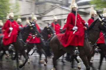 Royal guards on horseback dressed in ceremonial red coats pass in a parade on a rainy day in London, England, UK